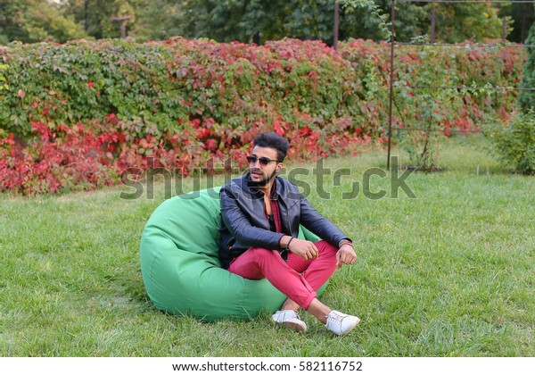 Arabian Young Man Sitting and Resting From City Bustle in Soft Green Chair and Looks Around. Handsome Guy Has Dark Hair and Black Beard and Wearing Maroon Shirt Over Black Leather Jacket and Bright