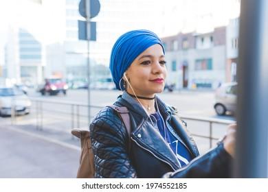 Arabian young woman wearing hijab outdoor listening music