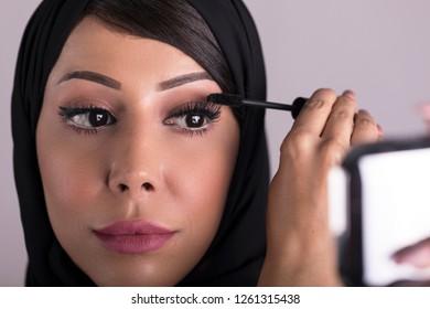 Arabic beauty model girl looking in the mirror and applying mascara make up. Beautiful Arabic woman apply makeup. Arab cosmetics concept.