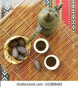 Arabic black coffee served in traditional coffee cups and jug with basket of dates. A rustic set up from above.