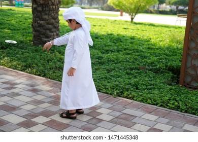 Arabic boy on his back wearing white kandura dress