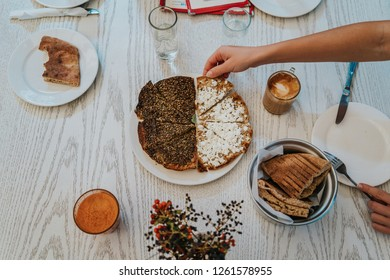 Arabic breakfast. Hand taking a piece of za'atar, typical food in Jordan, Lebanon and Syria, made with thym. Drinking coffee in a restaurant. Arab culture with pita bread.