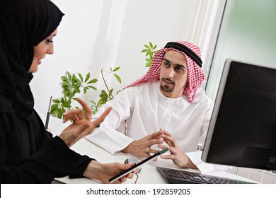 Arabic business couple working in office using tablet and computer.