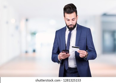 Arabic business man holding a smartphone and credit card, Business Banking