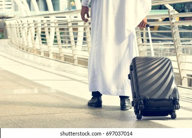 Arabic businessman holding suitcase luggage walking on terrace in the morning on modern city background while going to airport for business meeting and travel summer vacation trip with copy space area