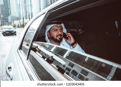 Arabic businessman looking at the skyline in Dubai from his limousine