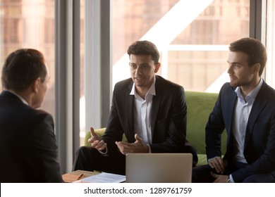 Arabic businessman talking at group meeting convincing client promising benefits, confident arab adviser speaking making business offer negotiating with caucasian partners presenting idea to investor