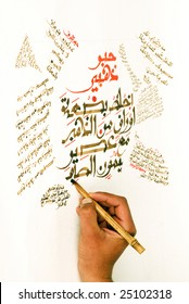 Arabic calligraphy being written by the artist using a hand made pen