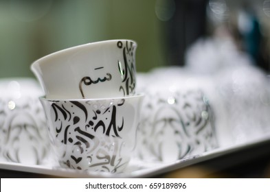 "Arabic coffee cup (the translation of the text appears on the cup: it is term used in Saudi Arabia means hospitality or it means ""here you are"" or it could means ""tell me what you want"")"
