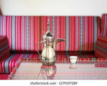 Arabic coffee. Coffee time served in a brass Arabic coffee jar with the blurred classic red Arabic seat in the background.