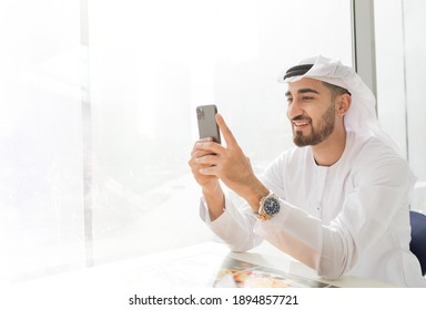 Arabic corporate business man wearing kandora looking at mobile phone and smiling - Portrait of traditional Emirati man