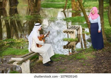 Arabic couple by the river with classical guitar