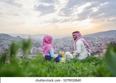 Arabic couple having a snack on the hill above a city