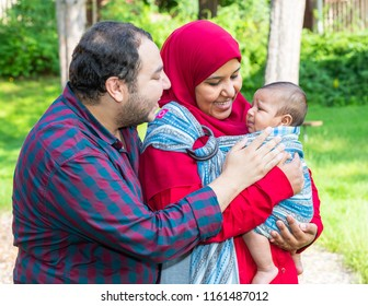 An Arabic couple is talking to their crying baby