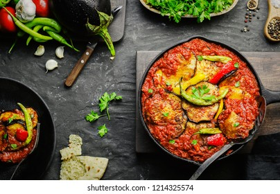 Arabic cuisine; Egyptian traditional food Moussaka. It contains fried eggplant(aubergine),colored bell peppers,chill peppers and garlic tomato sauce.Served with pita bread. Top view with close-up.