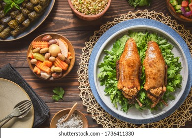 """Arabic Cuisine; Egyptian traditional stuffed pigeon or """"Hamam Mahshi"""" dish. Served with green salad, oriental pickles, cooked Freekeh and stuffed vine leaves. Close up with copy space."""