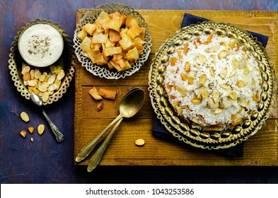Arabic cuisine; Jordanian Chicken Mansaf of white rice,crispy fried bread,topped with chucks of chicken, garlic yogurt sauce and toasted almond on copper plate.Top view