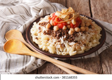 Arabic cuisine: kushari of rice, pasta, chickpeas and lentils close up on a plate on the table. horizontal
