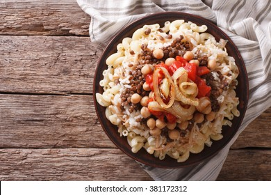 Arabic cuisine: kushari of rice, pasta, chickpeas and lentils on a plate horizontal top view