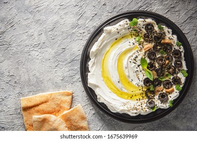 """Arabic Cuisine: Middle Eastern delicious dip """"Labneh"""". Cream cheese dip with olive oil, herbs and olives served with traditional pita bread. Top view with copy space."""