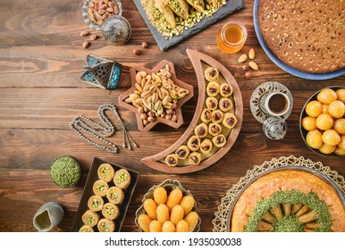 Arabic Cuisine: Middle Eastern desserts. Delicious collection of Ramadan traditional desserts. Served with tasty nuts, Arabic coffee, honey syrup and sugar syrup .Top view with close up. - Shutterstock ID 1935030038
