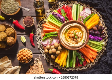 Arabic Cuisine;  Middle Eastern Hummus platter with assorted snacks. Hummus dip with fresh vegetables sticks, falafel,chickpeas,pita bread,olive oil and whole grain crackers. Top view with close up.