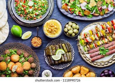 Arabic cuisine; Middle Eastern traditional dishes. Stuffed vine leaves,olives,hummus,pita bread,falafel, sambusak, kibbeh, shish tawook, meat kebab, tabbouleh and fattoush salad. Halal food. Top view.