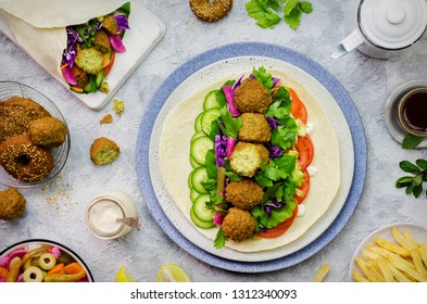 Arabic cuisine; Middle Eastern traditional Falafel wrap. Delicious Falafel and fresh vegetables ready to roll in pita bread. Served with pickles, tahini sauce, french fries and cup of tea with mint.