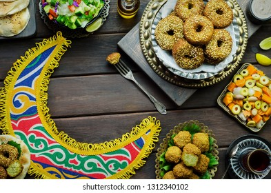 Arabic cuisine; Middle Eastern traditional Falafel dish. Varieties of fresh vegetarian Falafel patties served with green salad, pickles, pita bread, tahini sauce and lemon. Top view with copy space.