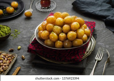 "Arabic Cuisine; Middle Eastern traditional dessert/Ramadan dessert ""Zalabya"", or Luqmat Al-Kadi served with honey, pistachio cinnamon, sugar and oriental tea. Close up with copy space."
