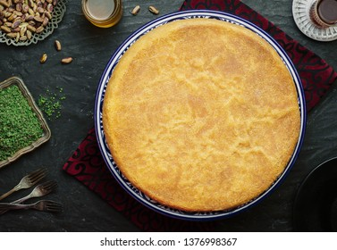 """Arabic Cuisine: Middle Eastern traditional pastries and Ramadan famous dessert """"Kunafa"""". Served with pistachi,honey syrup and cup of tea. Top view with close up."""
