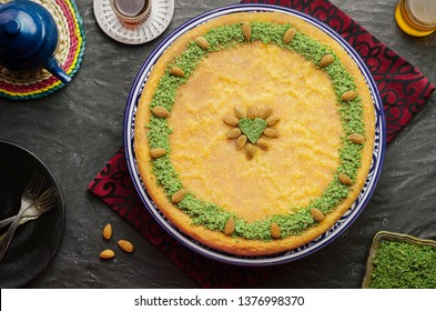 "Arabic Cuisine: Middle Eastern traditional pastries and Ramadan famous dessert ""Kunafa"" topped with crushed pistachio and roasted almond. Served with honey syrup,cup of tea with oriental kettle"