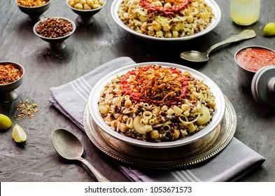 Arabic cuisine; Traditional Egyptian food:Delicious Kushary or Koushari of rice,pasta,chickpeas,lentils,crispy fried onions,fresh lemon and tomato garlic sauce on a plate.