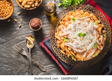 """Arabic Cuisine; Traditional Lebanese """"Chicken Fatteh"""" includes chickpeas,toasted pita bread and shredded chicken. Topped with warm garlicky yogurt sauce, fresh parsley and toasted pine nuts.  - Shutterstock ID 1666896367"""