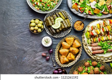 Arabic cuisine;Assorted of middle eastern traditional dishes. Stuffed vine leaves,olives, kibbeh, shish tawook, flafel, sambusak, tabbouleh and fattoush salad. Halal food. Top view with copy space.