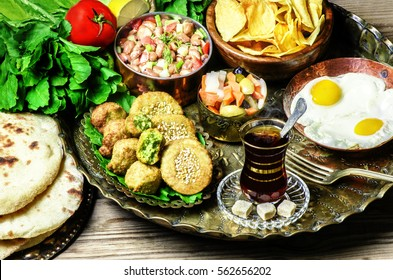 Arabic cuisine,Egyptian breakfast of fried egg, plate of Flafel,beans,pickles,chips, fresh organic vegetables,traditional baking bread and cup of tea in copper tray..
