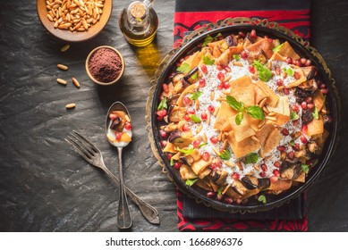 """Arabic Cuisine;Traditional Middle Eastern dish """"Eggplant Fatteh"""".This is a delicious mix of toasted pieces of pita bread and fried aubergine. Topped with garlicky-tahini sauce,pomegranate and pine nut - Shutterstock ID 1666896376"""