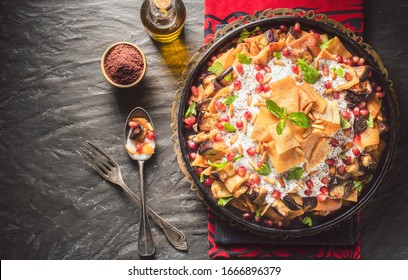 """Arabic Cuisine;Traditional Middle Eastern dish """"Eggplant Fatteh"""".This is a delicious mix of toasted pieces of pita bread and fried aubergine. Topped with garlicky-tahini sauce,pomegranate and pine nut - Shutterstock ID 1666896379"""