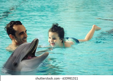 Arabic dad with his baby enjoying the swimming pool, dolphin