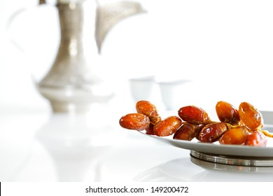 Arabic dates on a white plate with Arabic coffee pot of the Bedouin on a white background