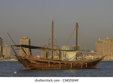 Arabic Dhow boat offshore in Qatar with its lateen sails furled and waterfront buildings visible behind