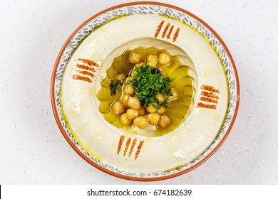 Arabic food Hummus with parsley in a traditional bowl.