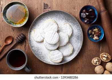 Arabic homemade cookies filled with dates and walnuts covered powdered sugar. Eid or Ramadan festival concept. Closeup view of top