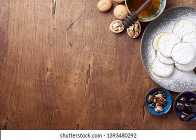 Arabic homemade cookies filled with dates and walnuts covered powdered sugar. Eid or Ramadan festival concept. Closeup view of top with copy space