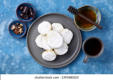Arabic homemade cookies filled with dates and walnuts covered powdered sugar. Eid or Ramadan festival concept. Closeup view of top on blue background