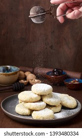 Arabic homemade cookies filled with dates and walnuts covered powdered sugar. Eid or Ramadan festival concept. Closeup view