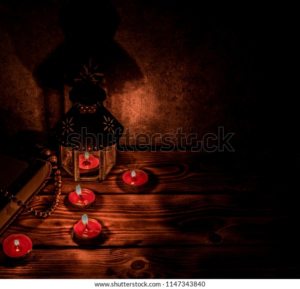 Arabic lantern with candle at night for Islamic holiday. Muslim holy month Ramadan. The end of Eid and Happy New Year. Copy space on dark background.