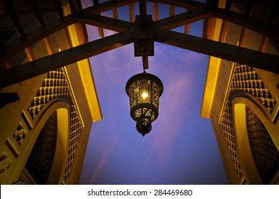 Arabic lantern hanging from a giant wooden arch. below angle.