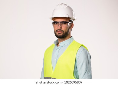 arabic latin engineer worker serious looking to camera , wearing safety helmet glasses and vest , isolated on white