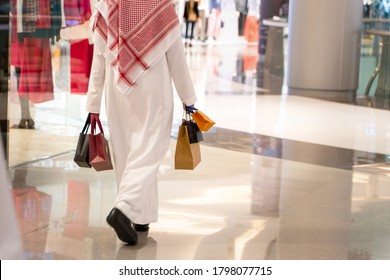 Arabic man holding shopping bags after buying some stuff from the mall